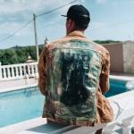 Jonge man bij zwembad in Ibiza met custom jasje met foto Johnny Depp en Kate Moss